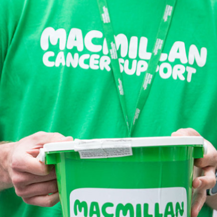 Person wearing a green Macmillan T-shirt holding a green Macmillan donation bucket